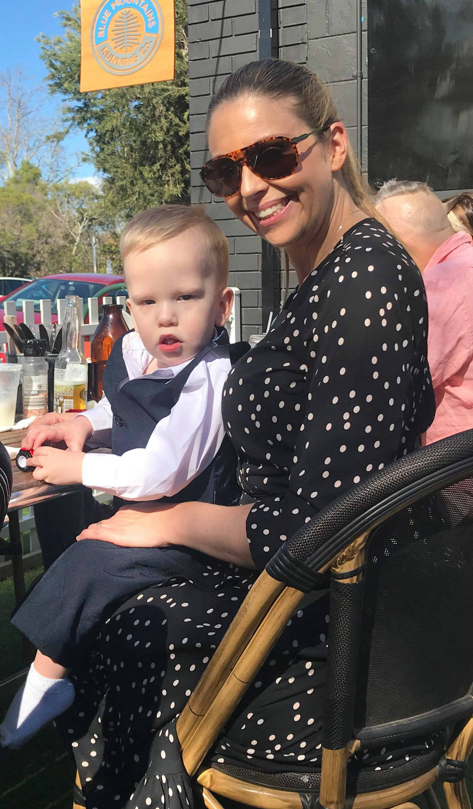 boy toddler sits on his mum's lap at an outdoor cafe