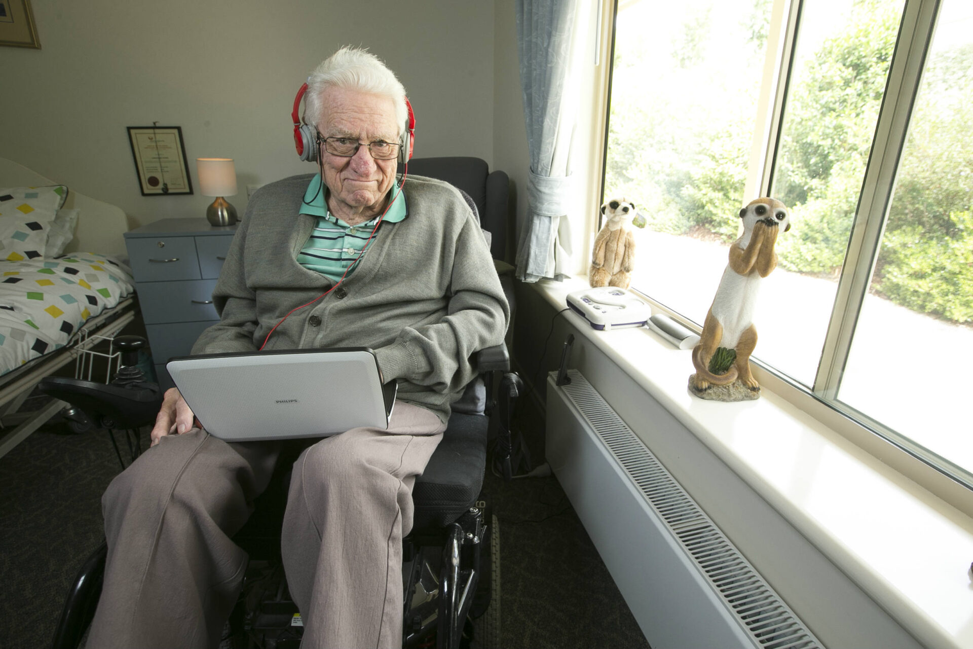 This is a photo of Gordon, in his room, sitting in a wheelchair next to his bed and beside a window. Gordon is wearing headphones and has a laptop on his lap. He looks into the camera with a wry smile. On the window sill are one stuffed toy meercat and one statue of a meercat.