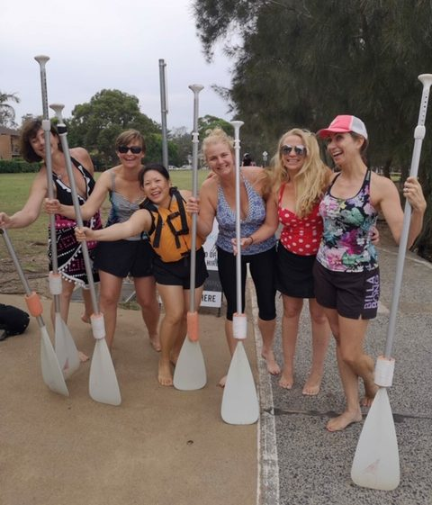 6 women posing, smiling, each holding a paddle. They are dressed in swimwear and shorts.