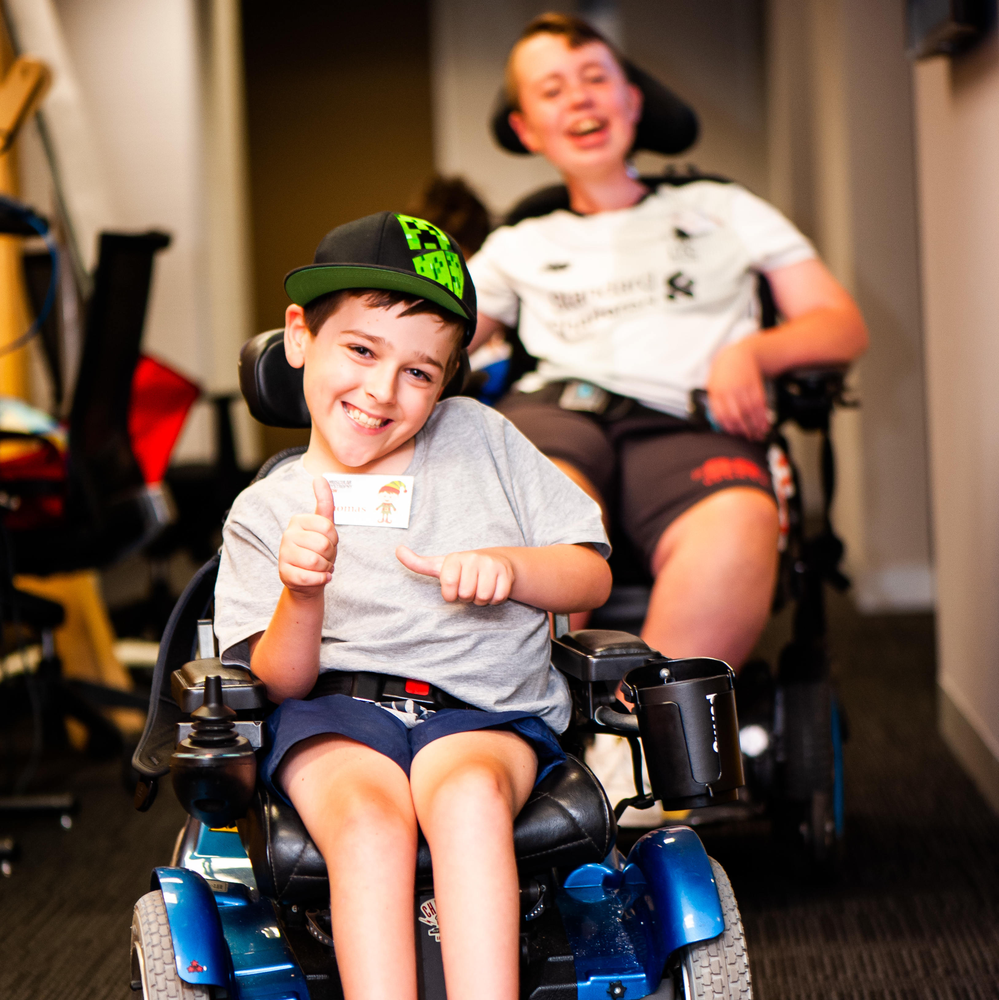shows two boys having fun in their power wheelchairs